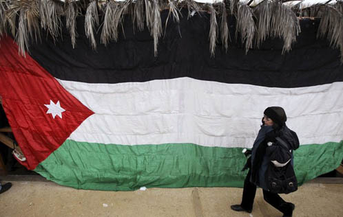 A pilgrim walks past a Jordanian flag. Source: Reuters/Muhammad Hamed