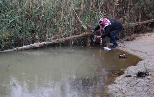 A pilgrim fills a plastic bottle with baptism water. Source: Reuters/Muhammad Hamed