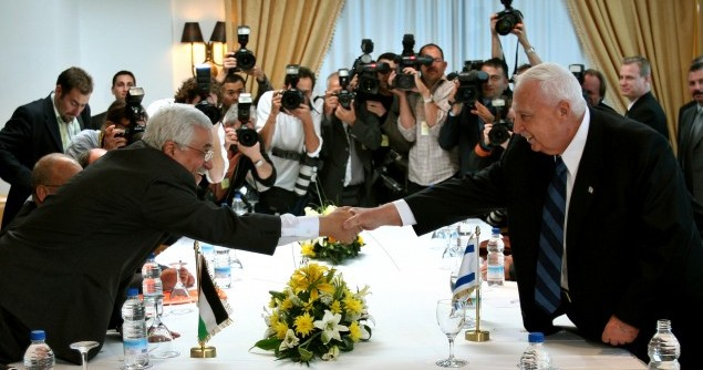 Palestinian President Abbas and Israeli Prime Minister Sharon shake hands at Sharm el-Sheikh.