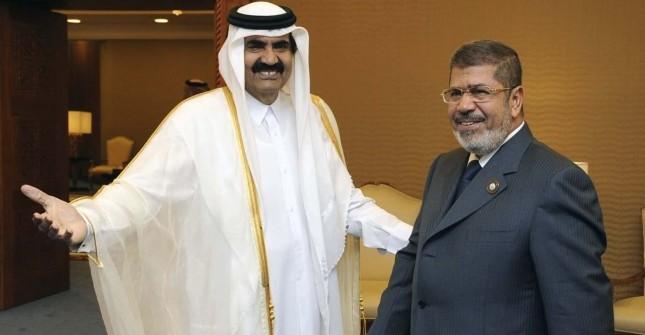 Qatar's Emir Sheikh Hamad bin Khalifa al-Thani greets Egypt's President Mohamed Mursi during the Arab League summit in Doha