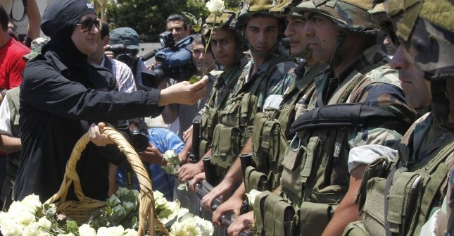 A female member of Intima party, offers flowers to Lebanese Army soldiers, during a demonstration near the Iranian embassy in Beirut