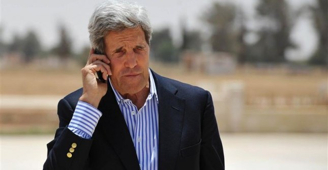 U.S. Secretary of State John Kerry speaks on the phone at Mafraq Air Base before boarding a helicopter to Amman, after visiting Zaatari refugee camp