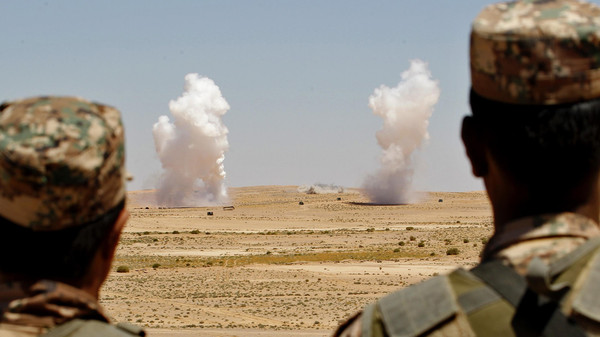 "Jordanian soldiers watch smoke rising during an artillery drill, part of the ""Eager Lion"" military exercise near the southern town of Al Quweira"